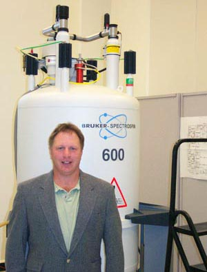Dave Kiemle standing near a NMR machine