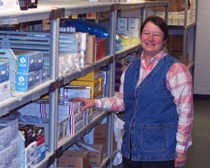 Marlene Braun standing next to shelfs stocked with laboratory supplies