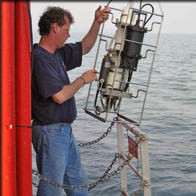 a researcher checks his data while working on a boat out inthe ocean
