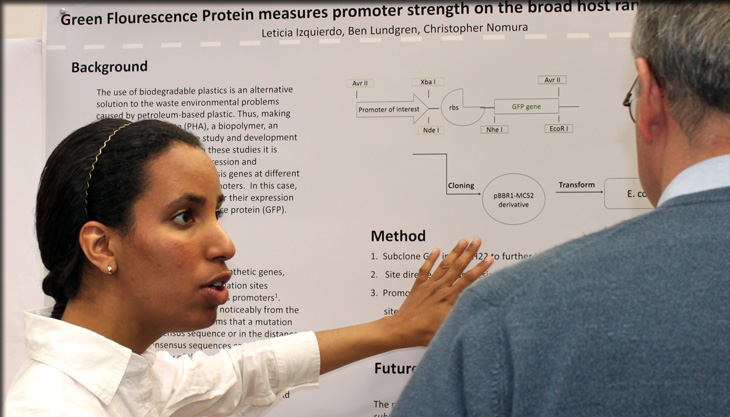 student explaining her research poster