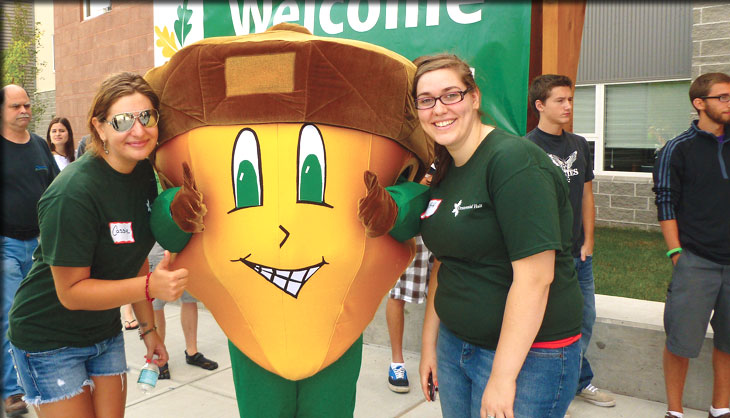 oakie the acorn posing with students