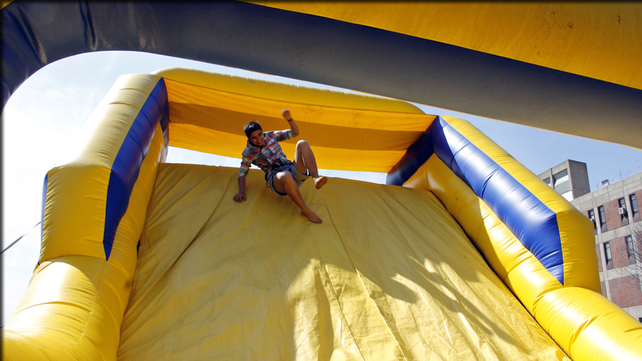 student on blow up slide