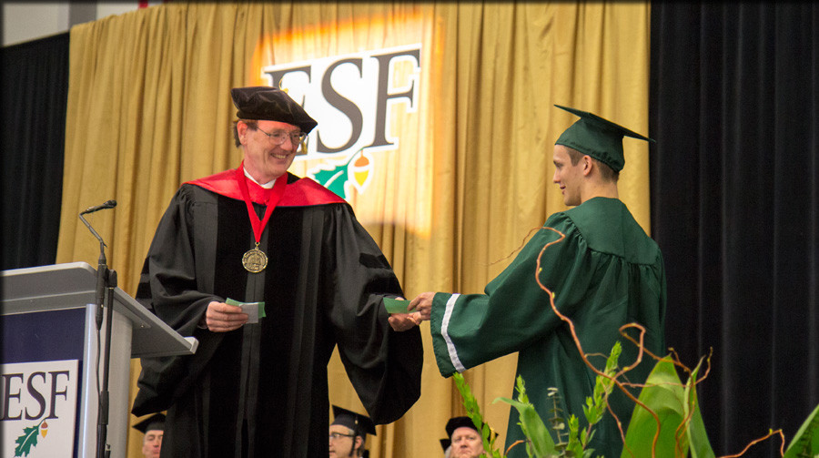 graduating student recieving diploma