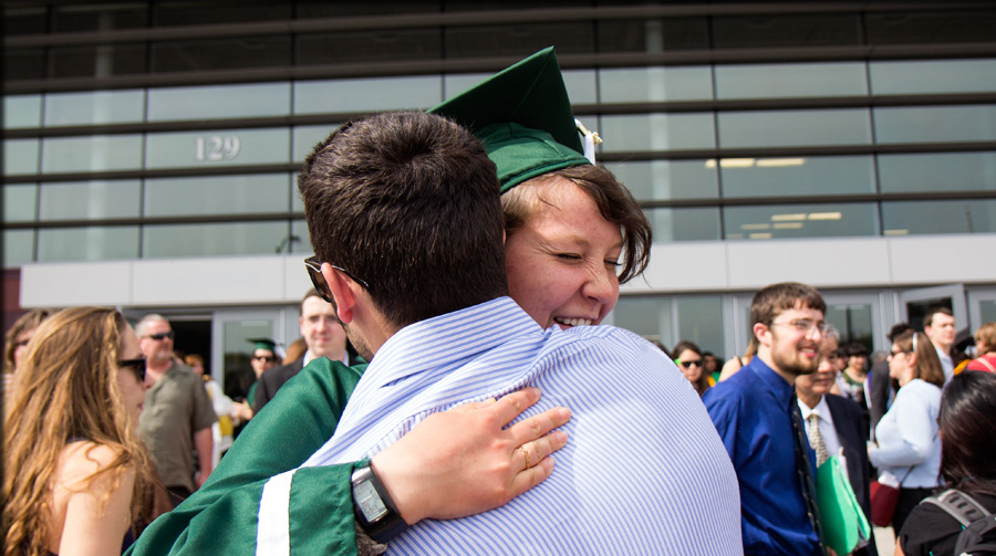 graduate hugging family