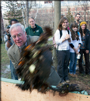 Students look on as President Neil Murphy loads the first shovelful of food waste and leaves into a new aerating composter.