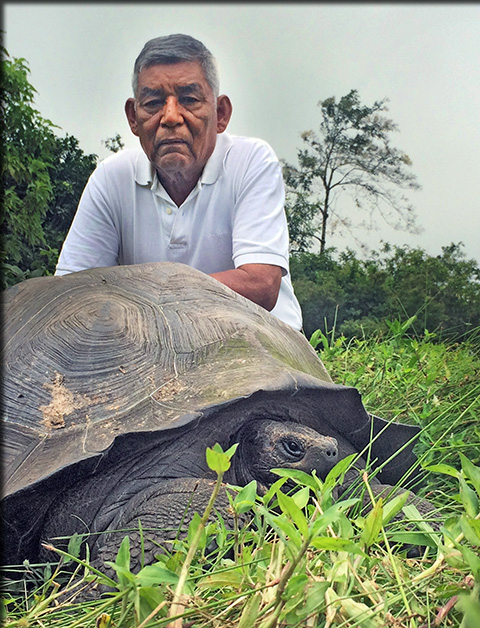 """Don Fausto"" poses with a tortoise from the species named in his honor. Image credit: Washington Tapia"