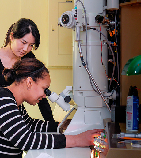 PhD. students Alisha Janae Lewis (seated) of Syracuse University and  Wenjun Cai of ESF work with an older transmission electron microscope in ESF