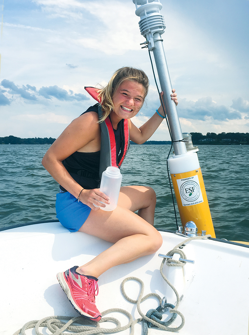 Kaela Natwora, an environmental chemistry major at ESF, works with a buoy that monitors water chemistry in Sodus Bay.