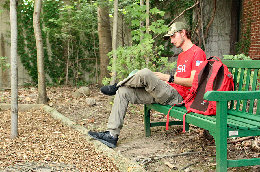 Alex Zamojski, a conservation biology major, takes a break in the Northern Hardwood Forest restoration site during his first day of classes.