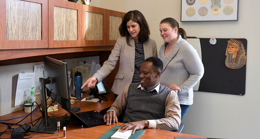 Dr. Ernest Nkansah-Dwamena, seated, helps deliver the online program. Contributing staff members are Kathy Lang, standing at left, and Ashley Gouger.