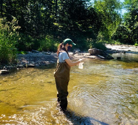 Delaney Demro, graduate research assistant and project manager on the CREEQ project, takes water samples in Central New York.