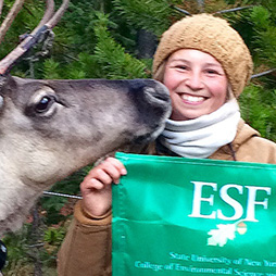 girl next to reindeer and holding e s f flag