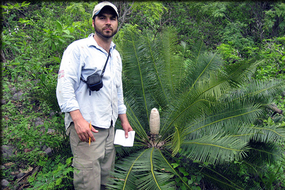 student next to a fern
