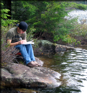 a student sketching by the river