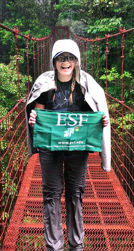 student on cable bridge holding E s f flag